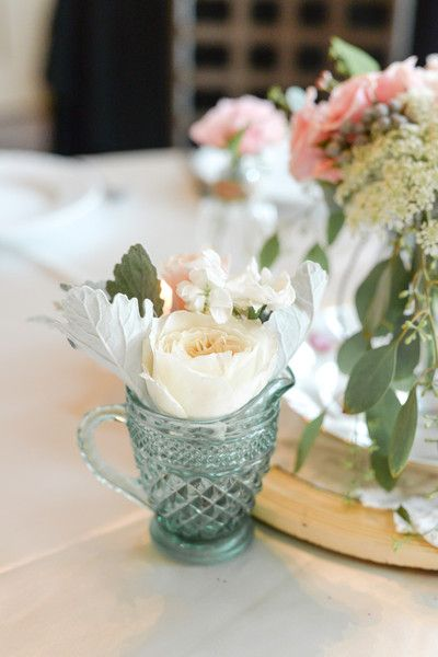 Vintage-inspired centerpieces with garden roses displayed in mini pitchers {Monique Hessler Photography}
