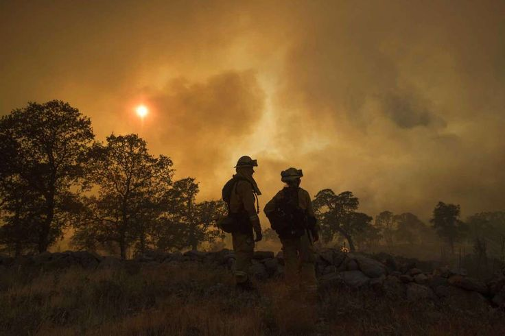 CalFire firefighter Jake Hainey, left, and engineer Anna Mathiasen watch as a wildfire burns near Oroville, Calif., on Saturday, July 8, 2017. The fast-moving wildfire in the Sierra Nevada foothills destroyed structures, including homes, and led to several minor injuries, fire officials said Saturday as blazes threatened homes around California during a heat wave. Photo: Noah Berger, AP / Noah Berger