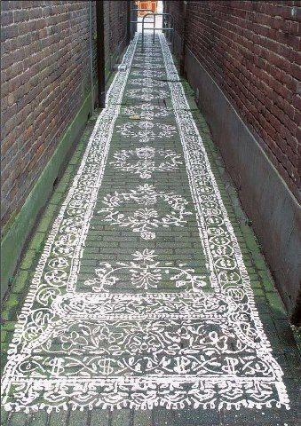 Narrow space between buildings painted to look like a rug.