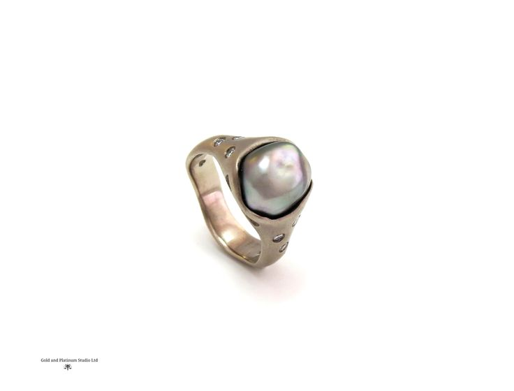 An unusual design. A Tahitian pearl set in platinum with diamonds set into the sides.