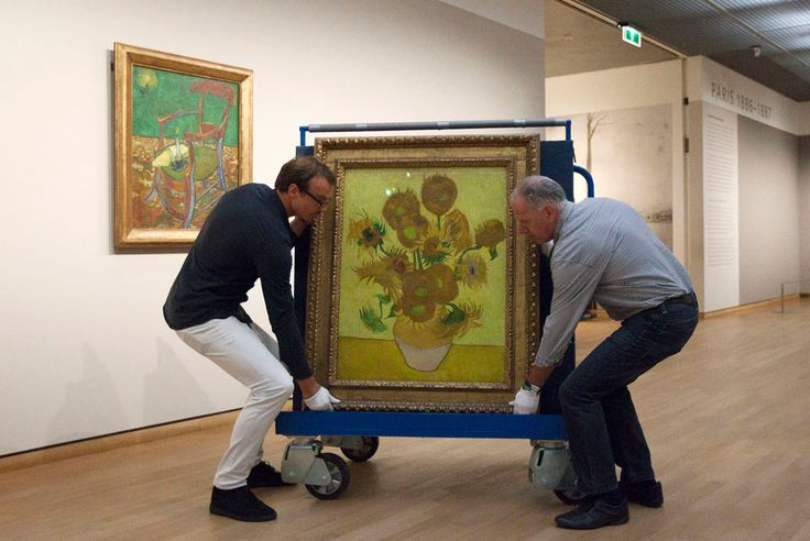 """""""Curators are putting Vincent van Gogh's famous """"Sunflowers"""" painting onto a felt-lined carrier trolley at the Van Gogh Museum in Amsterdam, Netherlands, Sunday, Sept. 23, 2012."""