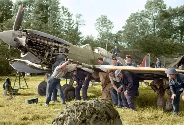 Men of an RAF Repair and Salvage Unit working on a damaged Supermarine Spitfire Mk IX of No 403 Squadron, Royal Canadian Air Force, at B.2 forward airstrip Bazenville in Normandy, 16-19 June 1944. Airfield Bazenville (Advanced Landing Ground B-2...