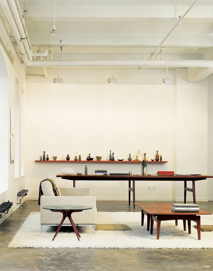 "The oversize conference table in Bob Weinstein's live/work loft (like the cocktail table in the foreground) was designed by Jens Risom, and, he says, ""supposedly came from the conference room of the Kinney Shoe Corporation."" Weinstein uses the table to display part of his Scandinavian pottery collection."
