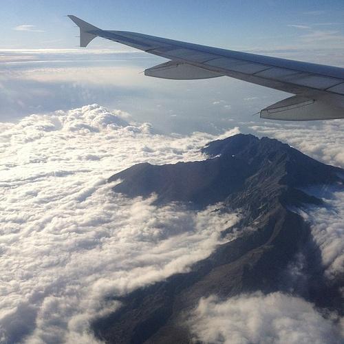 Greek island emerging over clouds