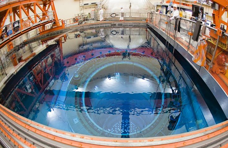 Workers are seen near an open reactor with fuel rods in a for Pool design reactor
