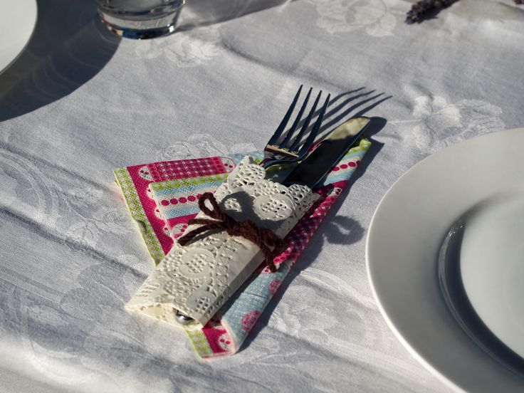 Cutlery for a outdoor dinner party.  Wrap in a doily and tie with wool.  Place colourful serviette underneath for colour.