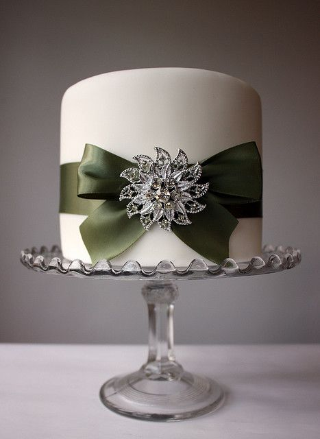 Elegant cake, single tier, fondant wrapped in ribbon with and adornment.