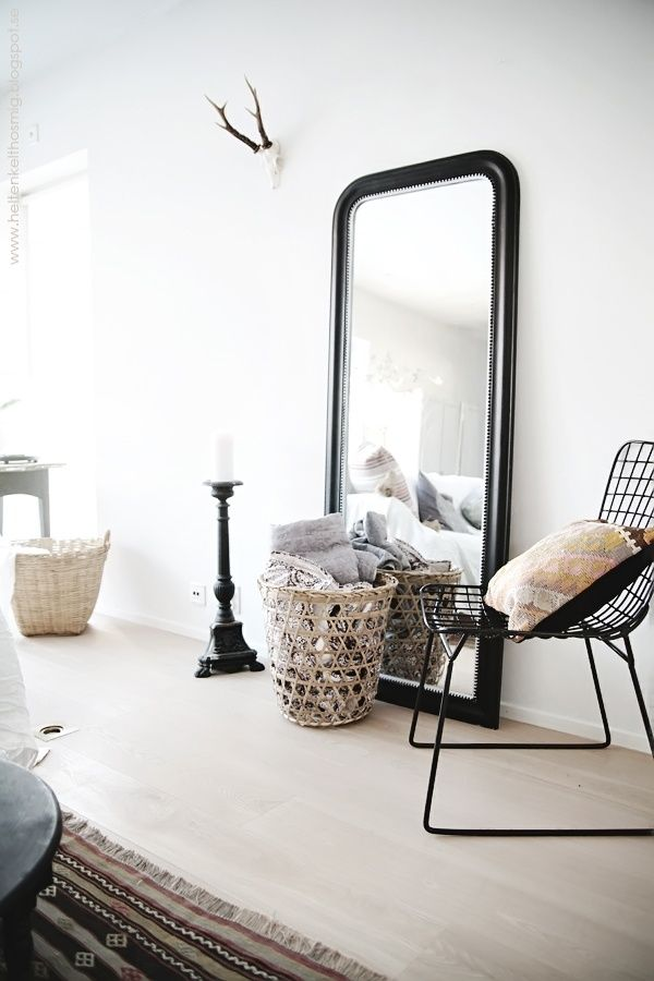 Scandi style bedroom with amazing huge black framed mirror balanced against one wall. Modern and sleek.