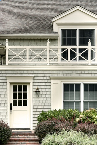 Shingle-style home, mudroom door, wood balcony railing.
