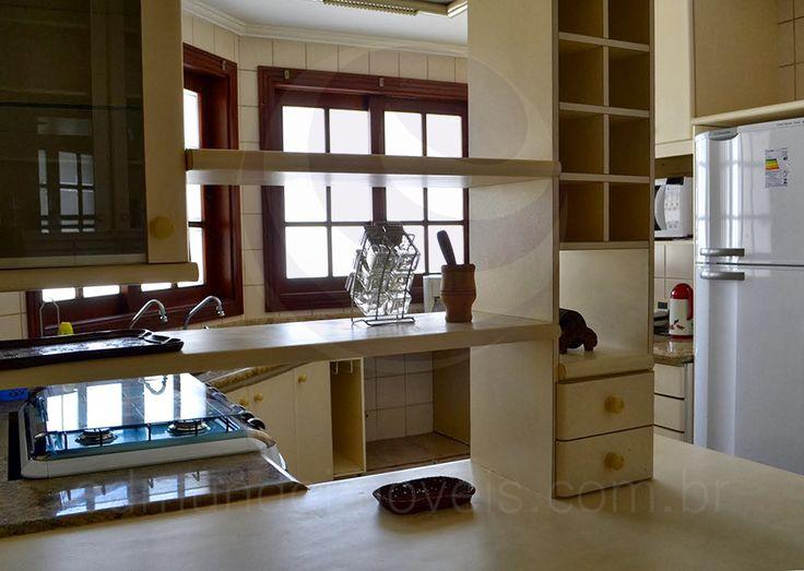 A cozinha planejada foi equipada com armários e nichos revestidos em fórmica em um delicado tom de amarelo pastel, além de bancadas em granito e eletrodomésticos de linha branca.