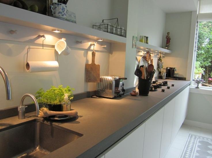Plankjes met lampjes boven aanrecht in donkere hoek keuken..