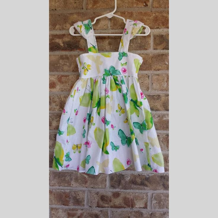 This beautiful dress features multiple layers of ruffles down the back for a fun design. Little flutter sleeves for a cute touch.