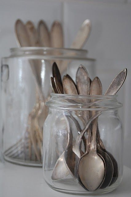vintage silver-ware in glass canisters, a very cool way to display them.