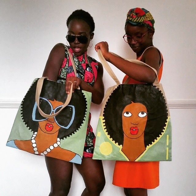 """Lupita Nyong'o in Kenya rocking a design by Nairobi-based satirist/artist Michael Soi— Via @lupitanyongo: """"What's not to love about our @soysos2 bags?! Thank you, Michael Soi. With assistant extraordinaire @kkaybie"""""""