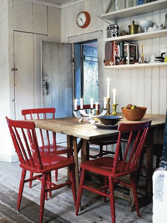 Swedish kitchen... I love the simple, wooden table paired with red wooden chairs. I also love the clock and shelves with various kitchen things displayed.