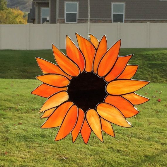 This beautiful stained glass sunflower suncatcher is made of hand cut glass. The pieces are individually wrapped in copper foil, and soldered. It comes ready to hang with a sturdy hook and clear line. It measures approximately 8 inches in diameter at longest points (each sunflower varies slightly as they are all hand made). The solder is waxed and buffed to shine. This suncatcher will look great in any window or hanging on a wall as a decoration. Glass colors: orange with yellow streaks and…