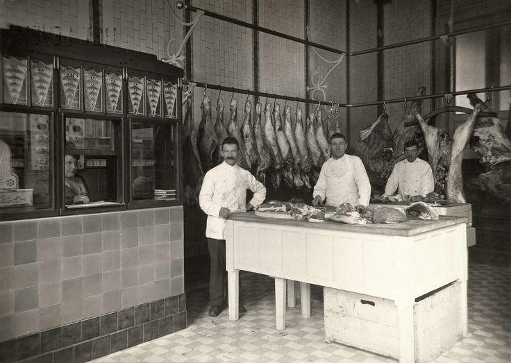 Interieur van slagerij Baruch in Amsterdam, met drie mannen in witte jassen bij het hakblok en verkoopster achter een loket. Nederland, 1919.