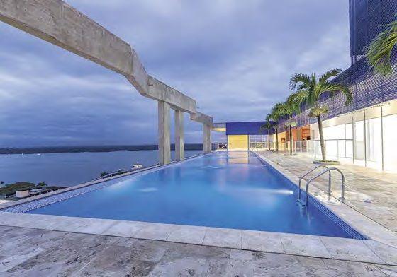 Las palmeras sembradas junto a la piscina sin fin brindan una atmósfera de costa en medio de un lugar con vista privilegiada hacia la ciudad y el puerto.