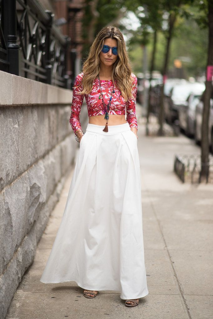 Greeting spring fashionably in a white maxi skirt and graphic crop top.