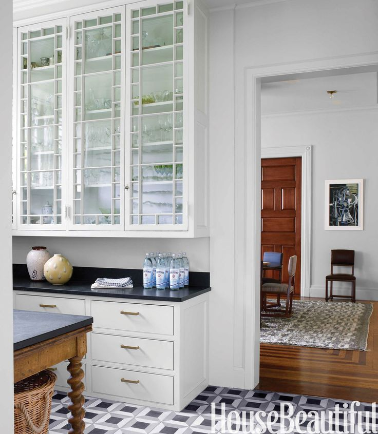 """Butler's pantry cabinets with original glass doors are painted in Farrow & Ball's Estate Emulsion in Shaded White, a color Tedhams used for the entire first floor because """"it has the incredible ability to be about 20 colors at once.""""   - HouseBeautiful.com"""