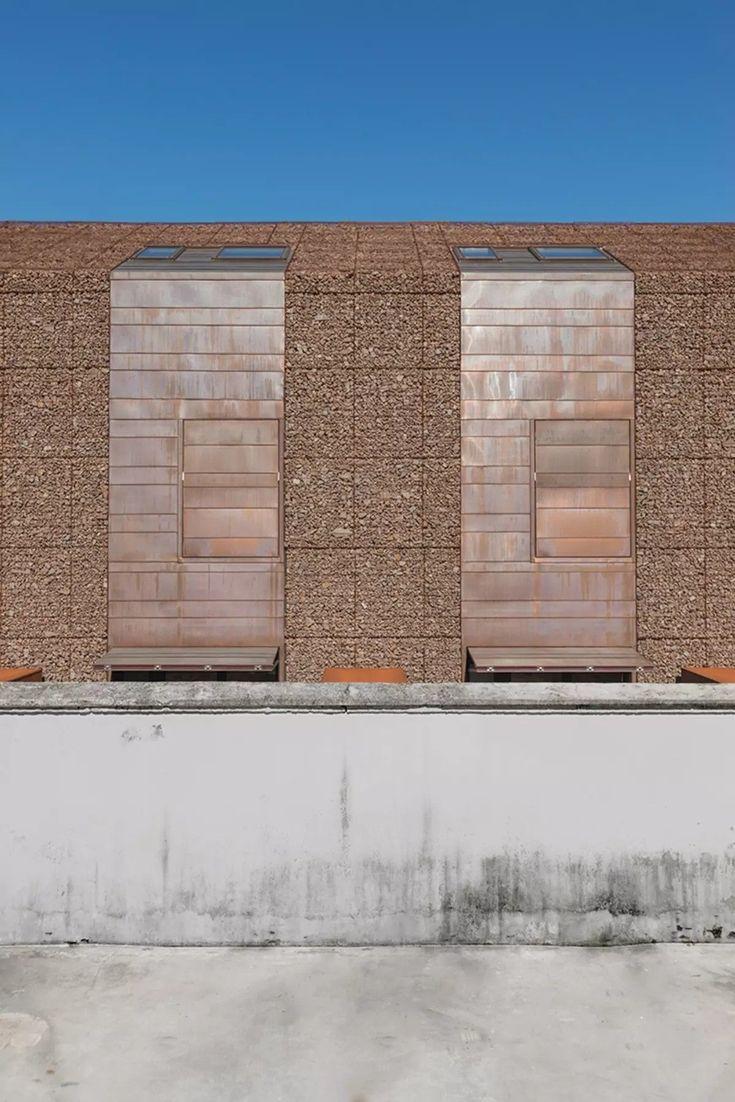 El conjunto reutiliza los escombros del derribo del antiguo edificio agricola que ocupaba la parcela -ladrillos de paredes y piedras de los pavimentos - como material de relleno para las nuevas fachadas de acero corten