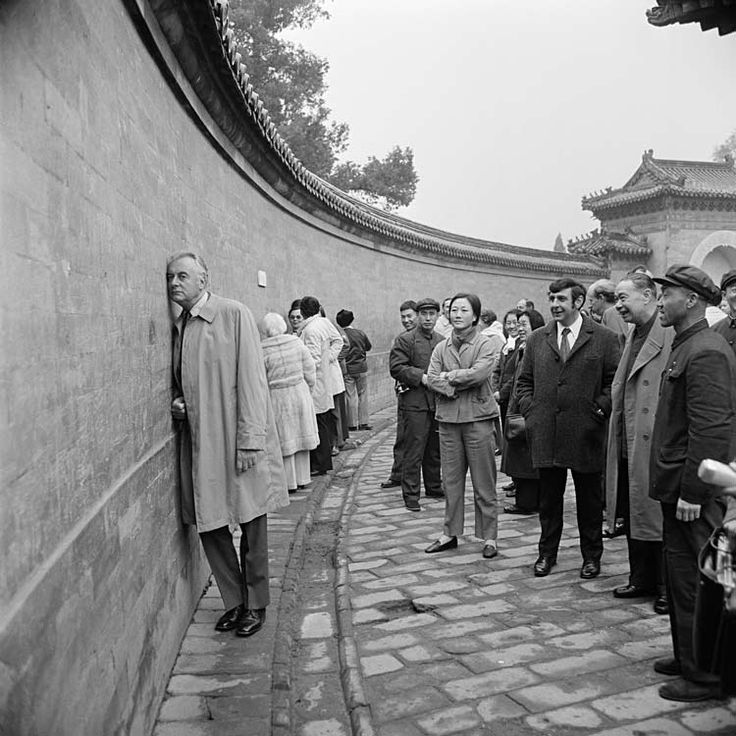 This is a black-and-white photograph of the Australian Labor Prime Minister Gough Whitlam during a trip to China between 31 October and 4 November 1973. Dressed in a long coat, Whitlam has his ear to part of the circular Echo Wall in the Temple of Heaven in Beijing. Further along the wall others are doing the same. Among a small crowd watching Whitlam is Australia's first ambassador to China, Stephen Fitzgerald, dressed in a coat and tie. Beside him, with her arms crossed, is a Chinese…