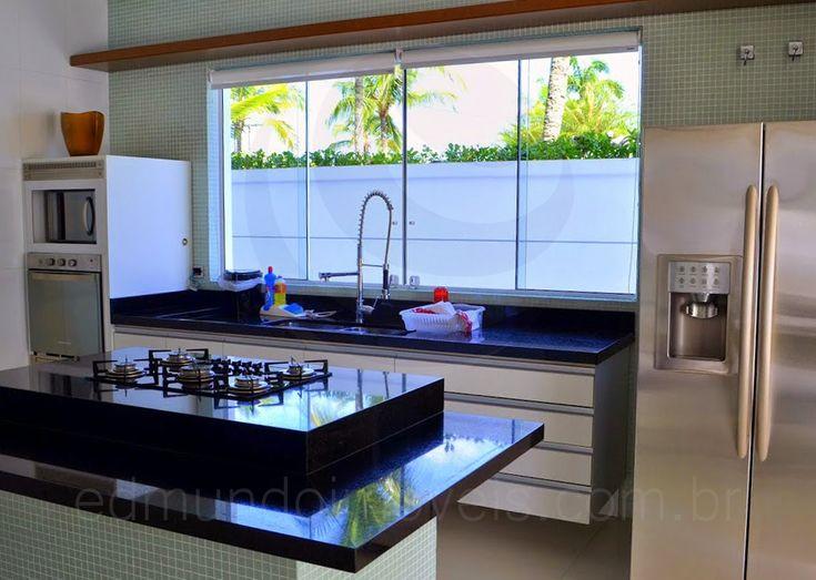 A cozinha é bem iluminada e tem ótimo arejamento, graças a duas amplas janelas sobre a bancada da pia. Equipada com eletrodomésticos em aço inox, armários planejados e ilha com cooktop, a cozinha foi parcialmente revestida com pastilhas de vidro em um agradável tom esverdeado.