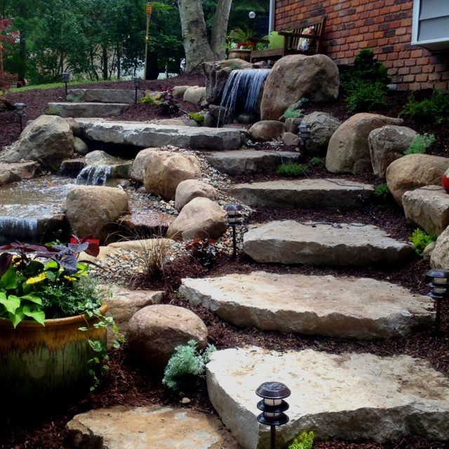 Cascading waterfalls along a limestone staircase via www.putsponds.com | Outdoor gardens, Hillside landscaping, Backyard landscaping designs