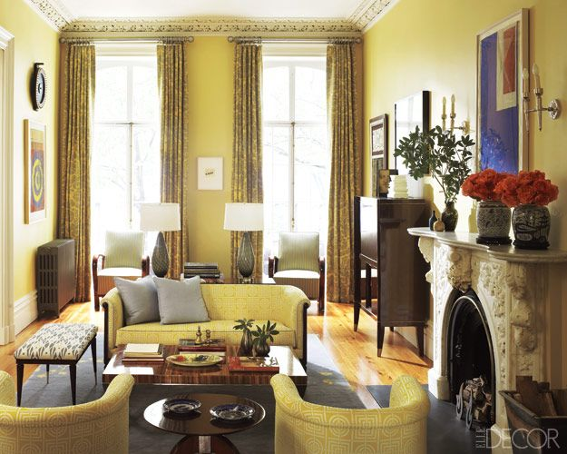 In the living room of a young family's Manhattan townhouse designed by Sheila Bridges, the crown molding and marble mantel are original, the curtains are of a Clarence House linen, and the armchairs and mahogany bar cabinet are Art Deco. The 1940s French sofa and chairs are upholstered in a Florence Broadhurst fabric, and the walls are painted in Farrow & Ball's Yellow Ground.    - ELLEDecor.com