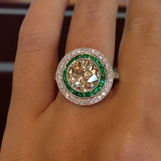 White diamond engagement ring with emerald accents