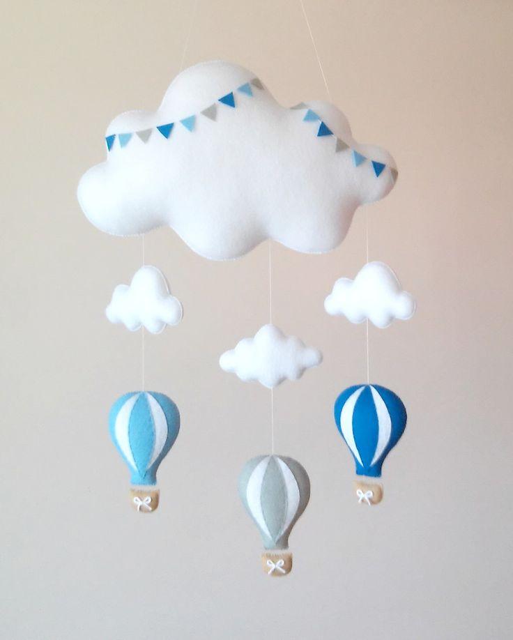Móbile feito de feltro, costurado a mão e preenchido com fibra siliconada.    Lindo móbile composto por nuvens e três balões. Sua leveza, o seu colorido e mobilidade traz calma e distração para o seu bebê.    Deixa qualquer ambiente alegre e divertido.    Medidas Aproximadas:    Altura: 90 cm ( D...
