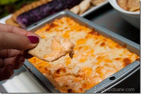 Buffalo Chicken Dip    2 poached chicken breasts, shredded  2 packages (8oz ea) neufchatel (low fat cream cheese), softened  1 cup low fat sour cream  3/4 cup Frank's RedHot buffalo wing sauce  1 teaspoon of garlic powder  1.5 cups shredded reduced fat cheese (I used 1/2 mozzarella, 1/2 cheddar), divided  Baby carrots and pita chips for dipping