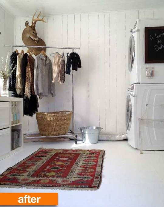 dark paneled room painted white, floor painted white, front load stacked, rolling rack for clothes that cannot be dried and ikea bookcase on its side to store detergent, etc.