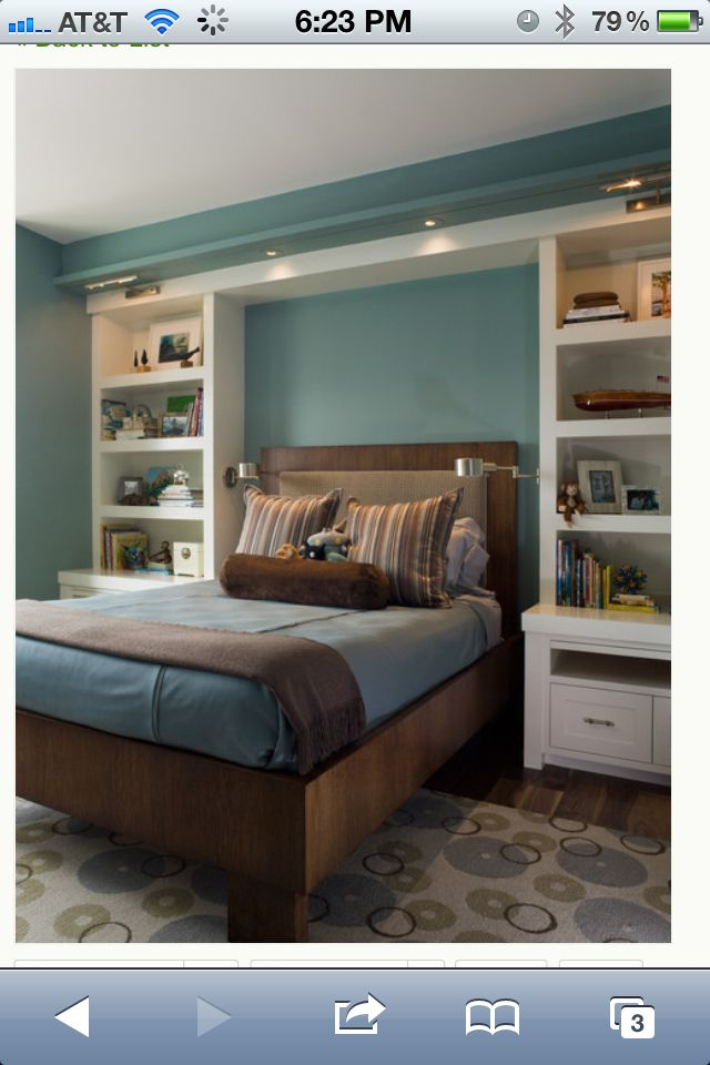 Blue bedroom walls  with built in shelves around bed