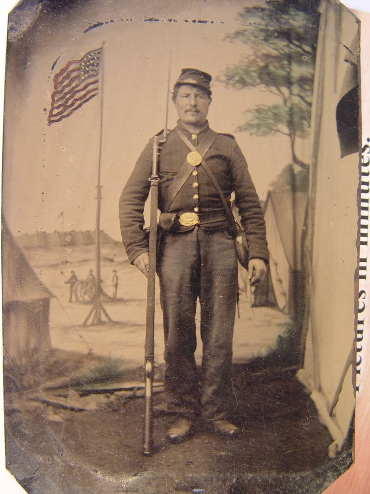 Unidentified soldier in Union uniform with bayoneted musket, canteen, cartridge and cap boxes in front of painted backdrop showing military camp with American flag.  From: Soldiers of the Civil War.