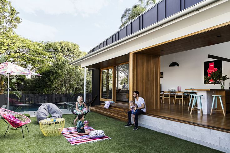 """Homeowners Laura and Alastair Stevenson play with their children, Andreas and Olivia, in the side yard of their revamped Brisbane home. """"Most of the time we're in the living and dining areas, spilling out onto the grass,"""" says Laura.   **Umbrella** from [Basil Bangs](http://www.basilbangs.com/