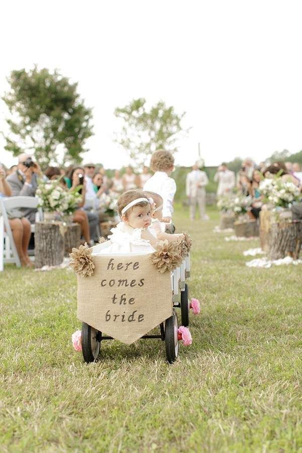 ring bearer pulls young flower girls in wagon @myweddingdotcom