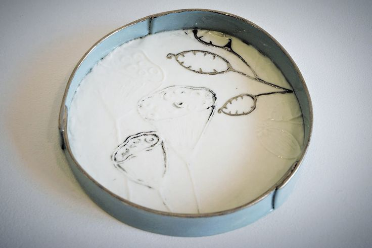 round wall plate made with recycled porcelain paperclay  with embossing printing patterns, black slip, finish with green turquoise slip and platinum lustre