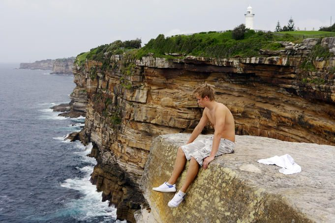 Young man sitting on edge of cliff at Vaucluse.