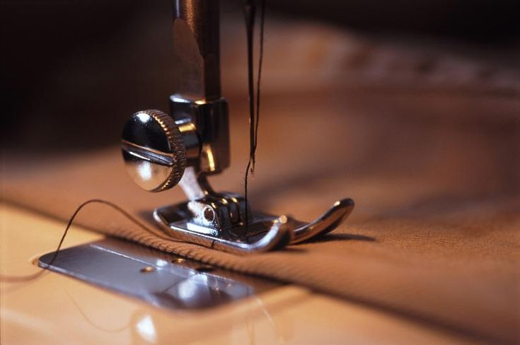 Close up of the foot and needle of a sewing machine threaded with black cotton in a low angle view with copy space - free stock photo from www.freeimages.co.uk