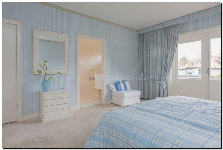 Woonstijl terug naar de kust in de slaapkamer met zomerblauwe muren en een witte barok spiegel.