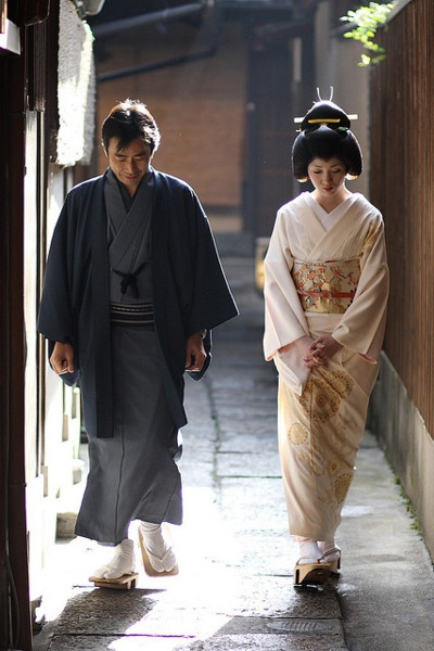 A couple wearing the appropriate kimono, going to or coming from their shinto wedding, and walking together.