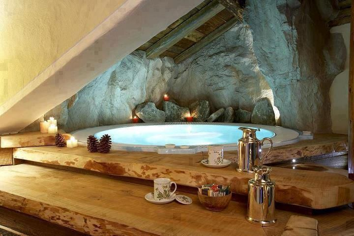 Get back to nature inside this stunning cave-like bathroom. The sunken bath, natural rock and wood provide an ideal chill-out zone.