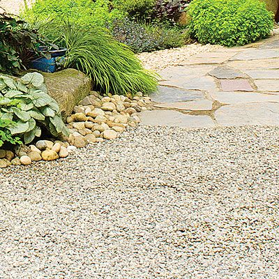 Both the multicolored flagstones set in sand and the ¾-inch granite gravel allow rainfall to pass through to plant roots. River rock edges the planting beds.