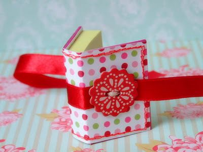 post-it notes... CUTE~looks like tiny BOOK; consider this idea for a tiny gift with a cross stitch piece on the front.  A small quilt block would also work.  The ribbon could be tied at the edges so as to not cover up the stitching.
