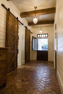 Dutch door, barn doors, herringbone brick floor, horizontal wood plank walls, wooden ceiling beam, transom windows and pendant lighting fixtures.