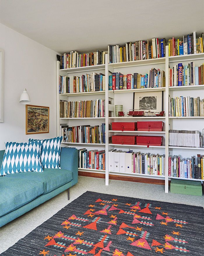A pressed-steel Parallel shelving system by Terence Woodgate holds books and mementos. Modern study with a shelving system for storing books