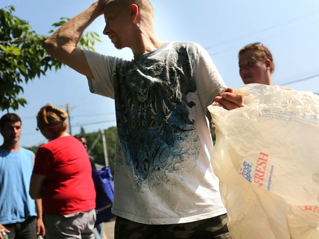 People wait in line with bags and boxes to carry food during a food distribution by the Food Bank of the Southern Tier Mobile Food Pantry on...