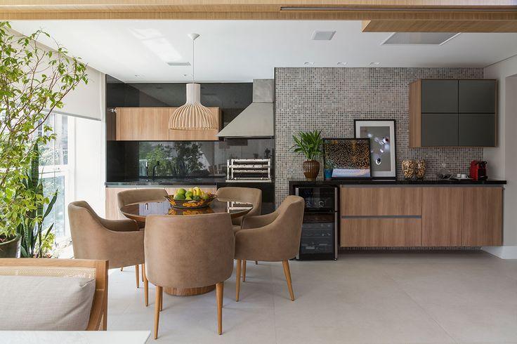 Decoração de apartamento moderno e integrado. Mesa de jantar de madeira redonda com cadeiras estofadas.
