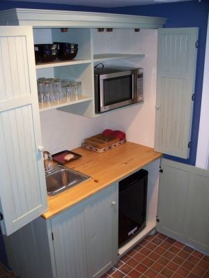 Armoire turned mini-kitchen. Great for guests who might stay in our basement